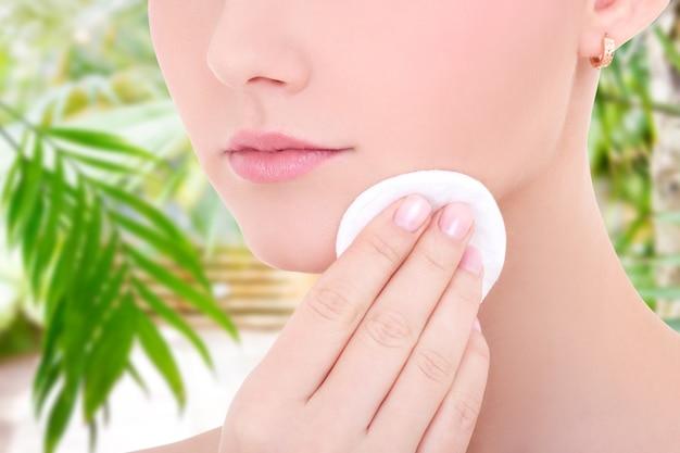 Feche o retrato de uma jovem mulher bonita limpando a pele do rosto com uma almofada de algodão