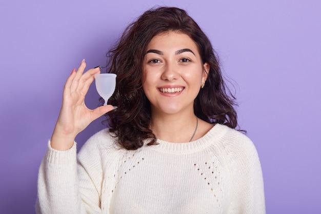 Feche o retrato de uma jovem mulher bonita sorridente segurando o copo menstrual em uma mão