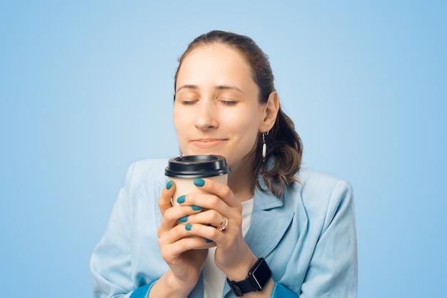Feche o retrato de uma jovem mulher cheirando seu saboroso café da manhã.
