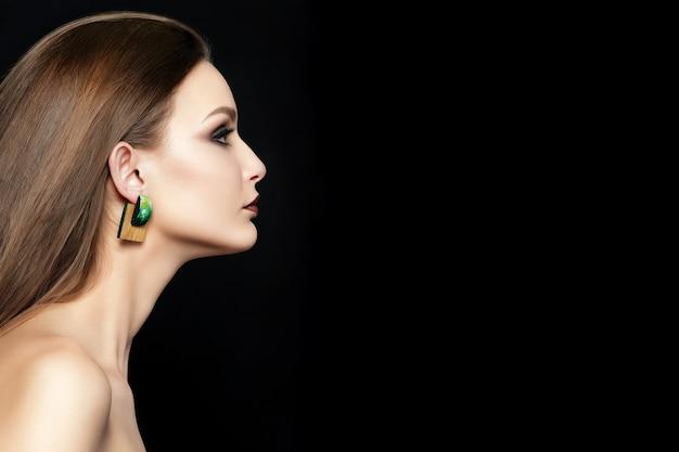 Feche o retrato de uma jovem mulher com lábios castanhos e olhos esfumados verdes sobre fundo preto.
