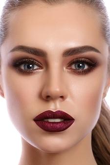 Feche o retrato de uma jovem mulher com lábios vermelho vinho e olhos esfumados bronze. a moda moderna compõe.
