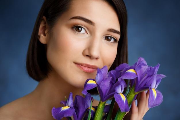 Feche o retrato de uma jovem mulher concurso com íris violetas sobre parede azul