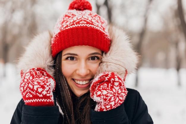 Feche o retrato de uma jovem mulher feliz, sorridente, muito sincera, com luvas vermelhas e chapéu de malha, vestindo um casaco de pele, andando brincando no parque na neve, roupas quentes, se divertindo