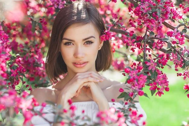 Feche o retrato de uma jovem mulher linda com uma pele lisa perfeita. senhora atraente em flores. retrato facial de mulher bonita.