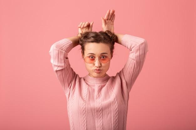 Feche o retrato de uma jovem mulher muito bonita com uma expressão engraçada no suéter rosa e óculos de sol, isolados no fundo rosa do estúdio, brincando