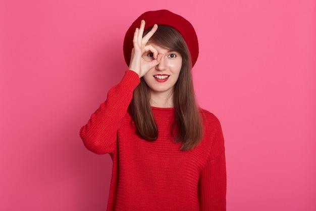 Feche o retrato de uma jovem mulher olhando através do sinal ok, adorável fêmea veste roupas vermelhas e boina, garota atraente, cobrindo o olho com um gesto bem, posando isolado sobre rosa