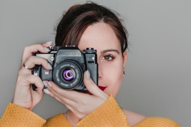 Feche o retrato de uma jovem mulher segurando uma câmera. conceito de fotografia