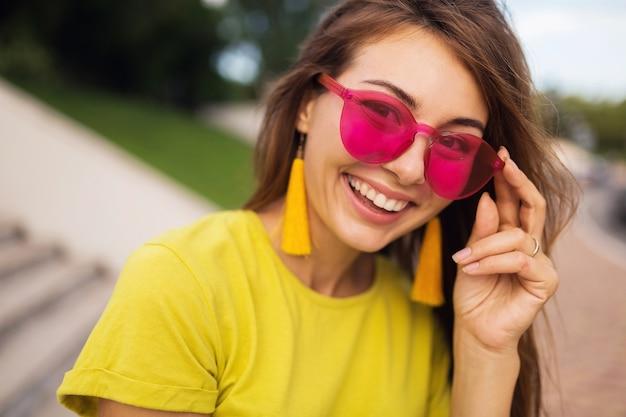 Feche o retrato de uma jovem mulher sorridente e atraente se divertindo no parque da cidade, positivo, feliz, vestindo blusa amarela, brincos, óculos de sol rosa, tendência da moda no estilo de verão, acessórios elegantes, coloridos