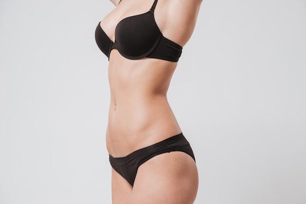 Feche o retrato de uma jovem mulher vestindo lingerie preta isolada na superfície branca
