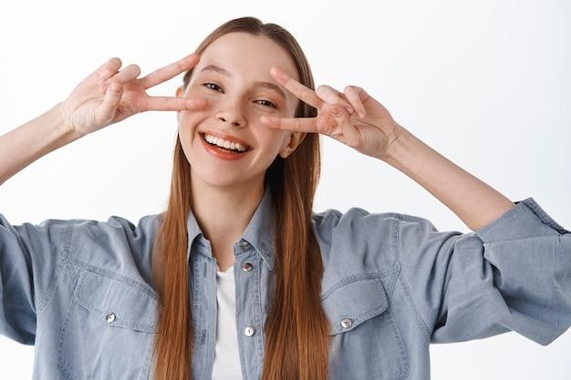 Feche o retrato de uma jovem positiva, mostrando o gesto de paz do sinal v e sorrindo feliz com os dentes brancos, em pé contra a parede do estúdio