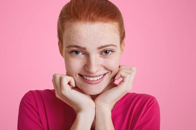 Feche o retrato de uma jovem positiva sardenta com olhar feliz, sorriso largo, tem cabelo ruivo, estar de bom humor como vai ter um encontro com o namorado. linda garota ruiva tem expressão alegre