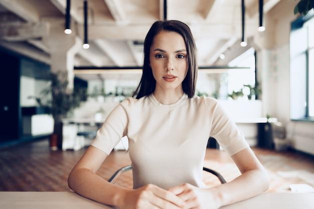 Feche o retrato de uma jovem que trabalha no escritório à mesa