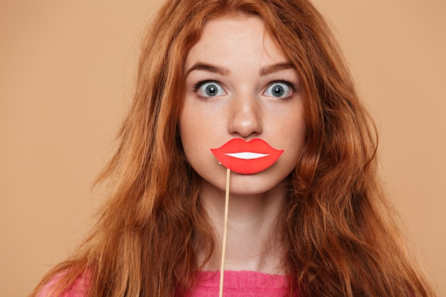 Feche o retrato de uma jovem ruiva com boca de papel de festa