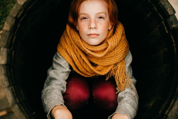 Feche o retrato de uma jovem ruiva com sardas, usando um lenço laranja, sentada no tubo redondo