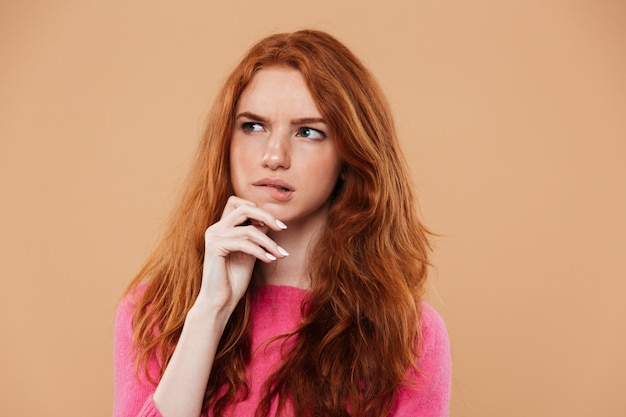 Feche o retrato de uma jovem ruiva pensativa
