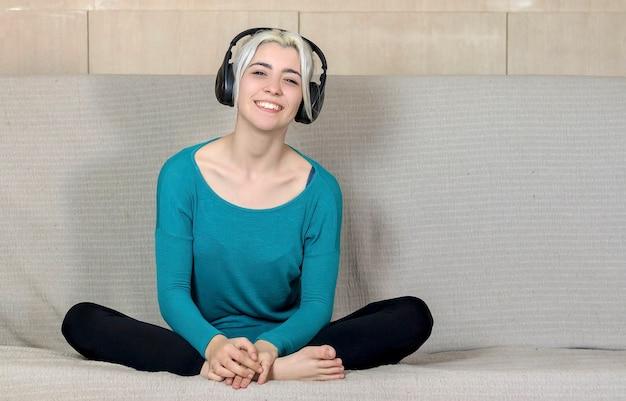 Feche o retrato de uma jovem sorridente com fones de ouvido enquanto está sentado no sofá e olhando a câmera