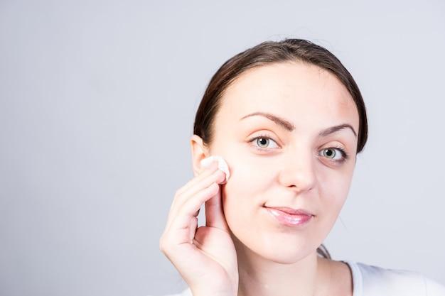 Feche o retrato de uma jovem sorridente, esfregando o rosto usando um algodão com limpador facial, enquanto olha para a câmera. capturado em estúdio com fundo cinza.