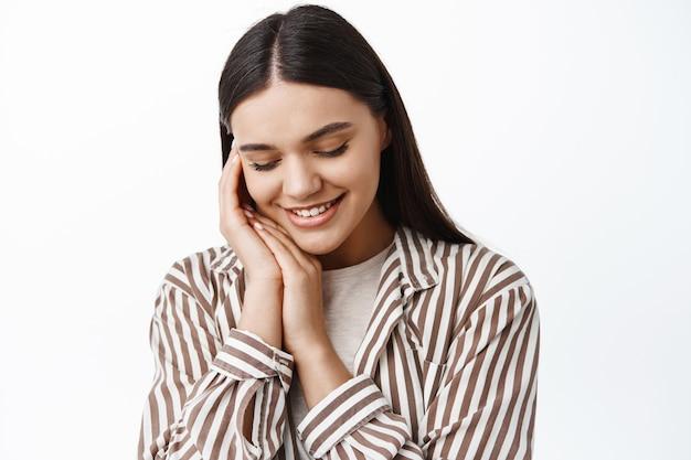 Feche o retrato de uma jovem terna e feminina, olhando para baixo e tocando a pele limpa e macia com maquiagem de luz natural, em pé sobre uma parede branca