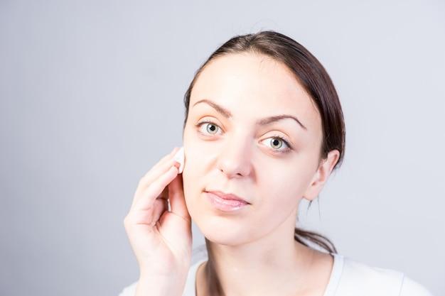 Feche o retrato de uma jovem vaidosa, limpando o rosto usando algodão com limpador facial, enquanto olha para a câmera. isolado em um fundo cinza.