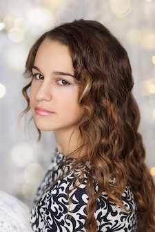 Feche o retrato de uma linda adolescente com cabelo comprido encaracolado