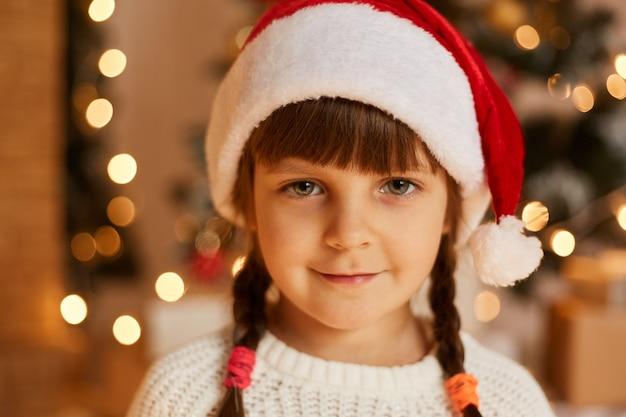 Feche o retrato de uma linda criança feminina encantadora, vestindo uma camisola branca e um chapéu de papai noel, olhando para a câmera com uma expressão positiva, estando de bom humor festivo.