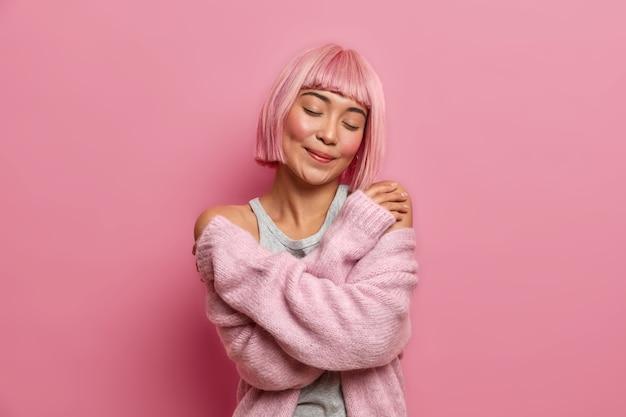 Feche o retrato de uma linda e encantadora mulher asiática com penteado rosa, se abraça, fica de olhos fechados, usa um suéter quente e macio, fica em pé