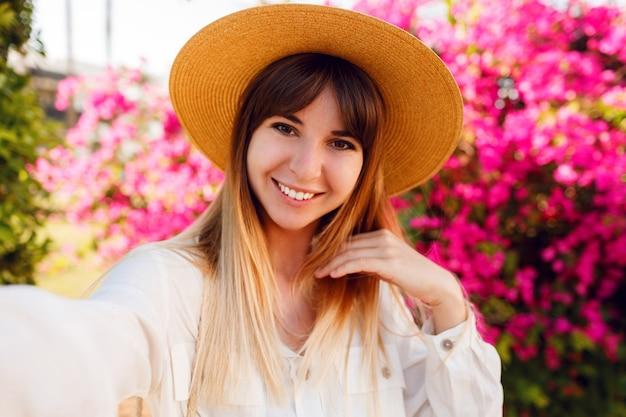 Feche o retrato de uma linda garota com um chapéu de palha da moda fazendo selfie retrato