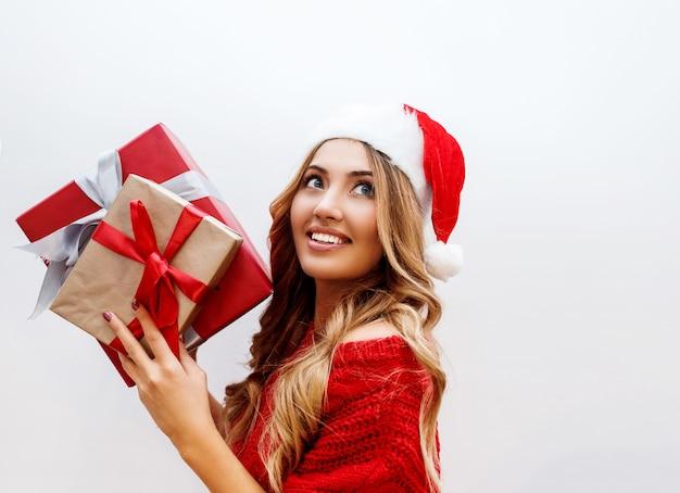 Feche o retrato de uma linda garota despreocupada com cabelos loiros ondulados brilhantes, posando com uma caixa de presente. usando suéter e chapéu de baile de máscaras de papai noel vermelho.