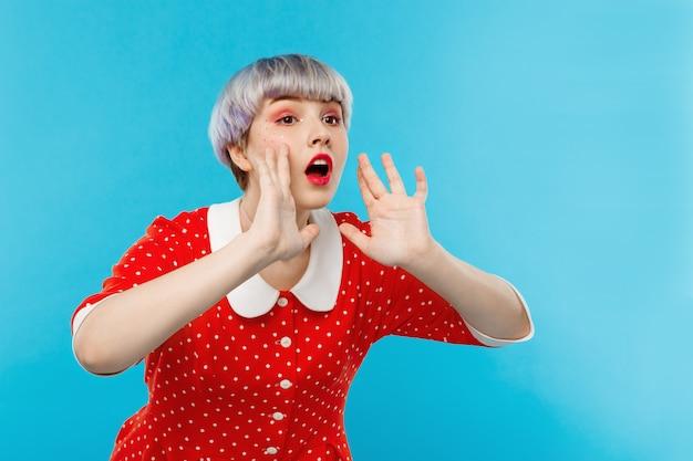 Feche o retrato de uma linda garota dollish com cabelo violeta leve curto, vestido vermelho, gritando sobre a parede azul