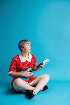 Feche o retrato de uma linda garota dollish com cabelo violeta leve curto, vestido vermelho, segurando o ukulele sobre parede azul