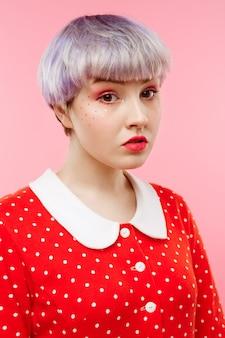 Feche o retrato de uma linda garota dollish com cabelo violeta leve curto, vestido vermelho sobre parede rosa