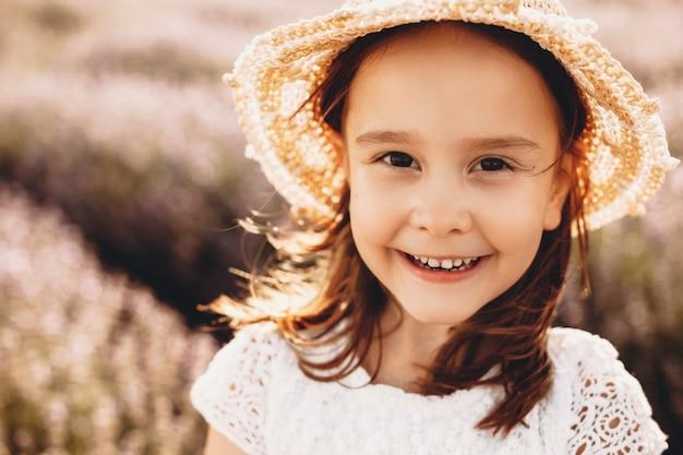Feche o retrato de uma linda garota olhando para a câmera sorrindo. criança bonitinha se divertindo ao ar livre em um campo de flores.