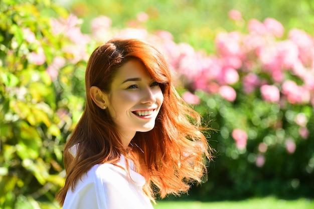 Feche o retrato de uma linda garota ruiva em pé sobre uma mulher com fundo de flor no jardim
