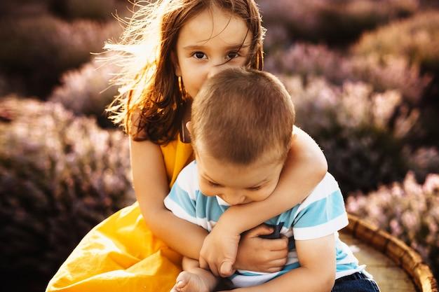 Feche o retrato de uma linda garotinha beijando na cabeça seu irmão mais novo enquanto o abraça contra o pôr do sol em um campo de lavanda.