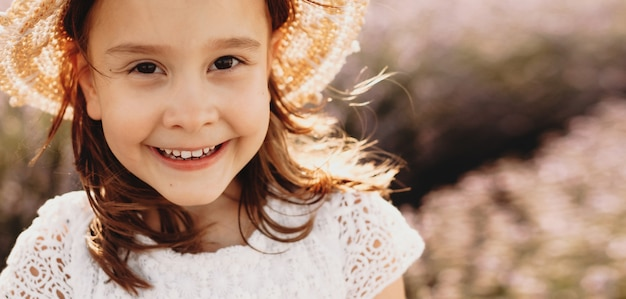 Feche o retrato de uma linda garotinha olhando para a câmera rindo enquanto usava um chapéu contra o pôr do sol em um campo de flores enquanto o vento soprava em seu cabelo.