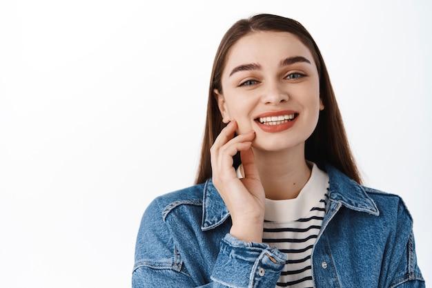 Feche o retrato de uma linda jovem sorrindo com dentes brancos perfeitos, tocando a pele natural limpa e fresca, em pé feliz contra uma parede branca em jaqueta jeans para sair