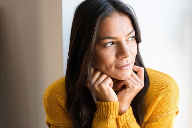 Feche o retrato de uma linda jovem vestida com um suéter sentada na janela dentro de casa