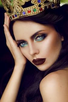 Feche o retrato de uma linda menina morena usando uma coroa