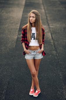 Feche o retrato de uma linda mulher adolescente bonita com um corpo perfeito em camisa vermelha, camiseta branca, shorts e tênis vermelhos