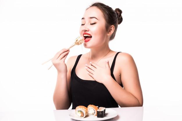 Feche o retrato de uma linda mulher comendo sushi rolls