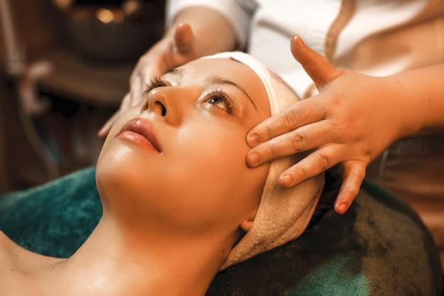 Feche o retrato de uma linda mulher encostada na cama do spa, fazendo massagem facial por um cosmetologista antes dos procedimentos faciais.