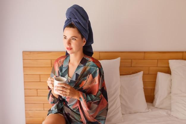 Feche o retrato de uma linda mulher envolto em toalha e roupão acordando de manhã sentado na cama e tomando chá