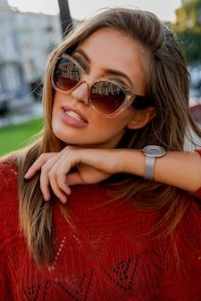 Feche o retrato de uma linda mulher europeia em óculos de sol posando ao ar livre. humor de outono. cabelos ventosos.