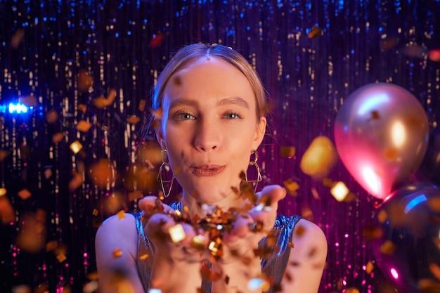 Feche o retrato de uma linda mulher loira soprando glitter para a câmera enquanto aproveita a festa na boate, copie o espaço