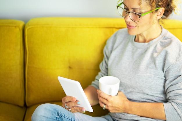 Feche o retrato de uma linda mulher madura lendo um livro no tablet com óculos, sentada no sofá
