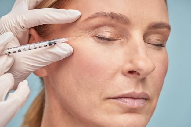 Feche o retrato de uma linda mulher madura mantendo os olhos fechados enquanto recebe ácido hialurônico