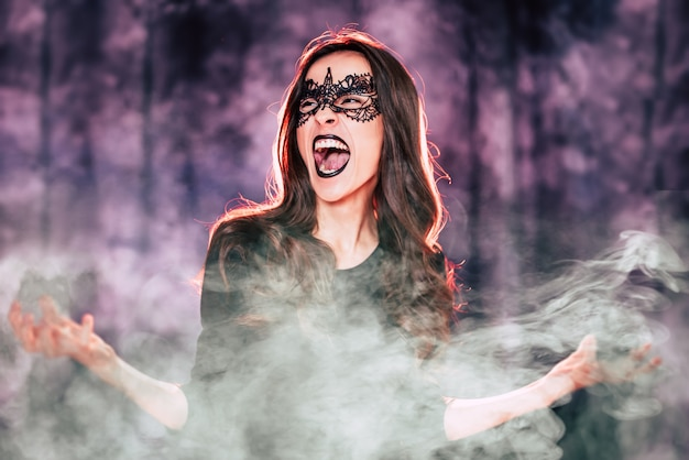 Feche o retrato de uma linda mulher morena fantasiada de bruxa, posando durante uma festa de halloween