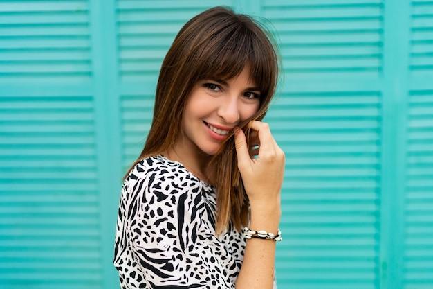 Feche o retrato de uma linda mulher posando sobre parede azul.