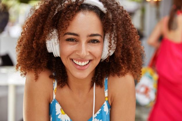 Feche o retrato de uma linda mulher sorridente satisfeita com a pele escura, tem cabelo crespo, aproveita o tempo livre durante as férias de verão em um café na calçada
