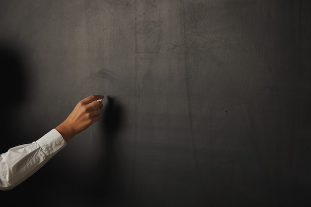 Feche o retrato de uma mão feminina segurando giz em uma lousa preta brilhante em branco